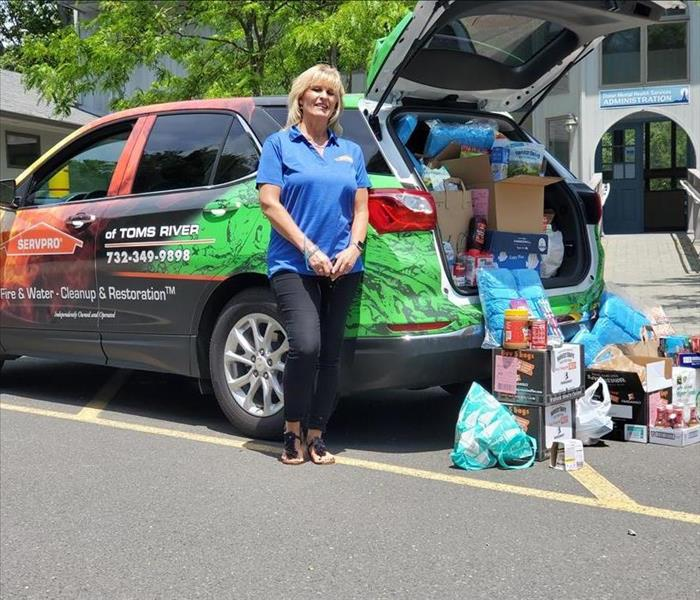 Kathy standing next to SERVPRO of Toms River with car full of food and personal items that were donated