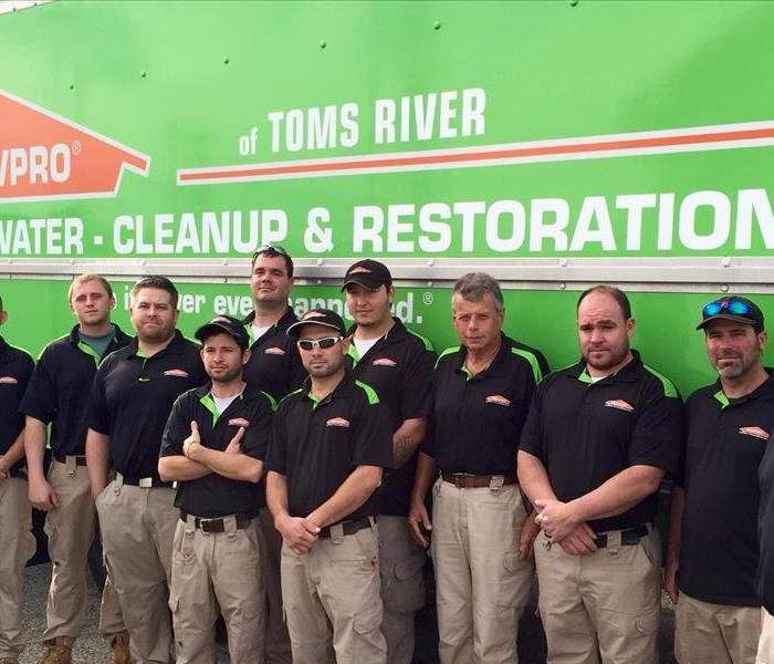 team members standing in front of a green SERVPRO truck