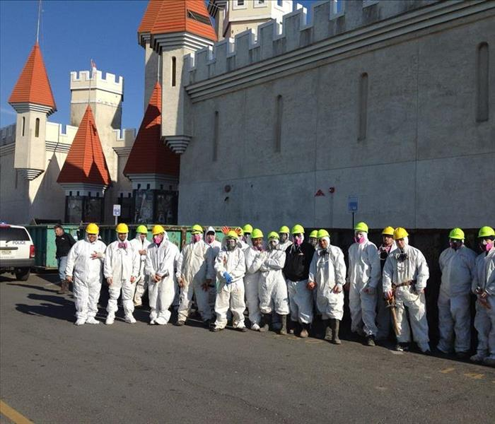 several employees dressed in PPE in front of a stone building