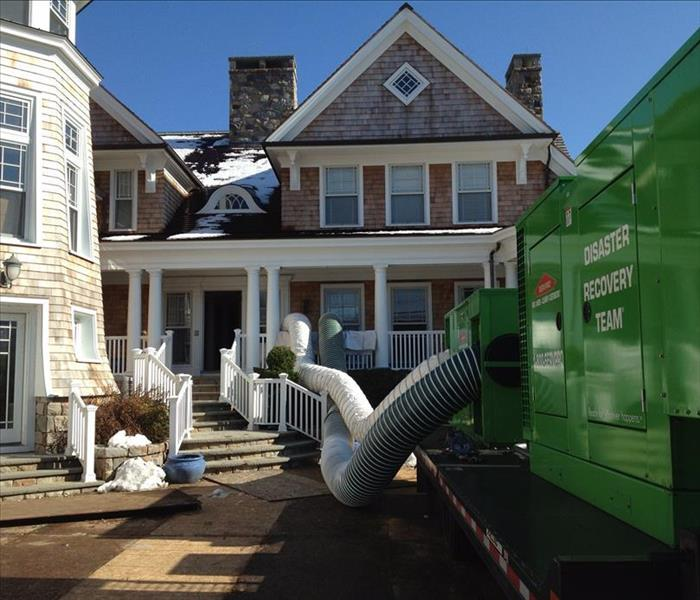 tan home with SERVPRO equipment on front driveway