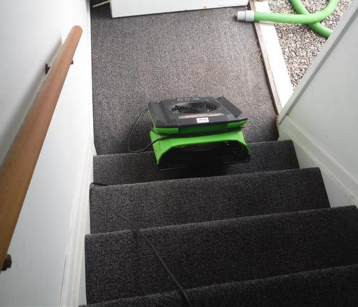 Water drying equipment at the bottom of a stairway with carpet